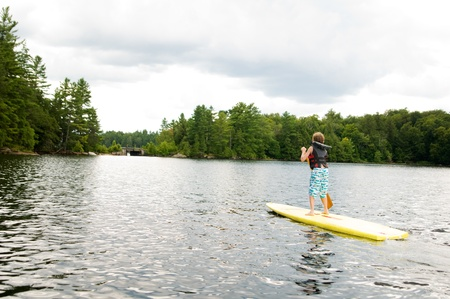 lifejacket: young boy stand up paddle boarding
