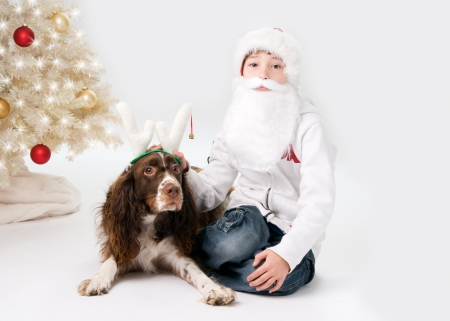 little boy dressed up as santa with his pet dog dressed up as a raindeer