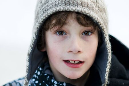 wooly: close up of an eight year old boy wearing a wooly winter hat outdoors in the snow
