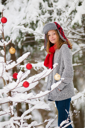 cute girl in a snowy forest decorating a tree with christmas ornaments photo