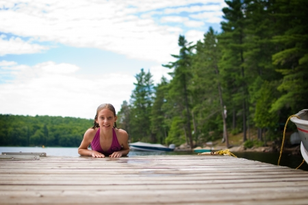 young teenage girl on a dock at a lake in Ontario's cottage country photo