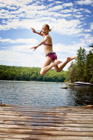 young teenage girl jumping off a dock at a lake in Ontario's cottage country