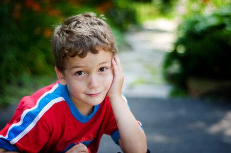 ojos marrones: adorable ni�o mirando a la c�mara con una sonrisa t�mida y grandes ojos marrones