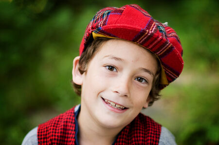 cute eight year old boy wearing a plaid scotish cap