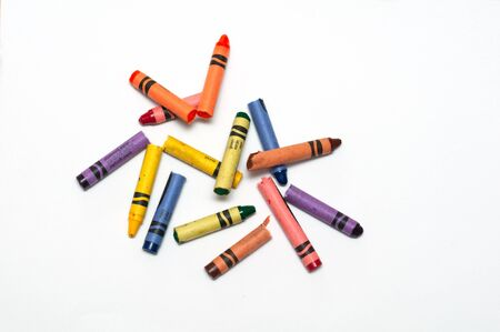broken crayons laying on a white sheet of paper