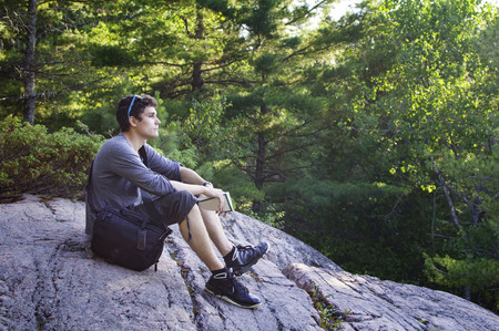soul searching: teenage boy sitting on a rock in a forest thinking
