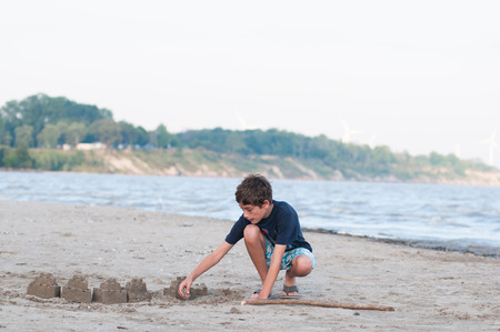 sandcastles: young boy on a sandy beach building sandcastles by the water