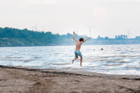 joyfull: happy boy jumping in the waves at a beach in summer