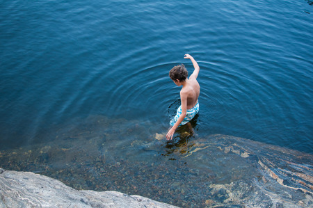 young boy wearing swim trunks getting into a lake from a rocky shore Imagens