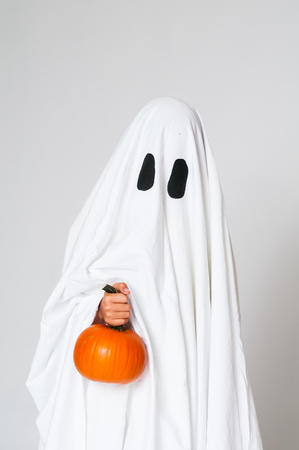 white sheet: young child dressed as a ghost holding a pumpkin for halloween Stock Photo
