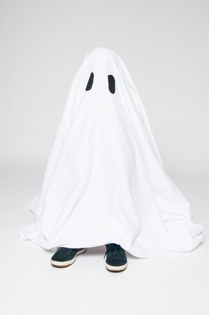 child dressed as a halloween ghost with his feet showing beneath the sheet