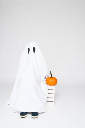 cute ghost: child dressed as a cute ghost sitting with a pumpkin