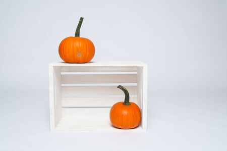 two bright orange pumpkins on a white crate Stock Photo