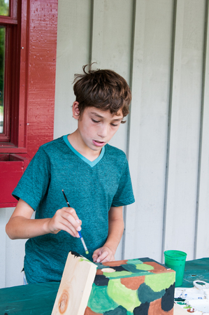 summer camp: boy at camp painting a birdhouse craft project Stock Photo