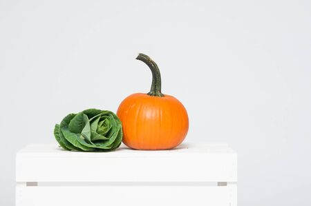 orange pumpkin and green cabbage on a white crate