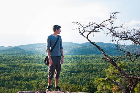 provincial forest parks: teenage boy standing looking at the veiw on a hike in Killarney Provincial Park