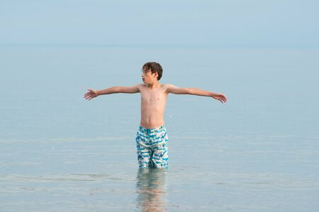 child standing in a calm lake with his arms outstreached