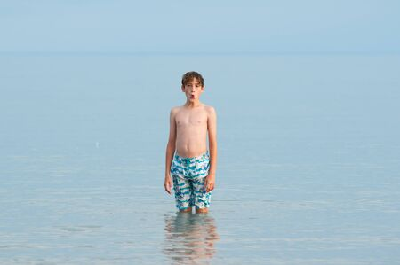 single child standing in a calm blue grey lake in his bathing suit
