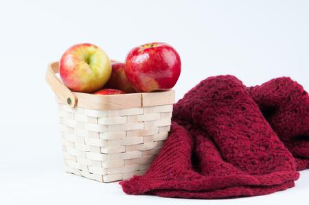 Backet di mele rosse e una calda coperta di lana su uno sfondo bianco Archivio Fotografico - 91130219