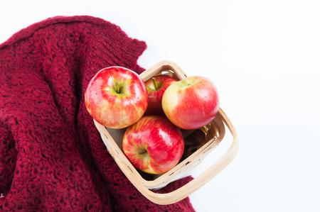 Backet di mele rosse e una calda coperta di lana su uno sfondo bianco Archivio Fotografico - 91130220
