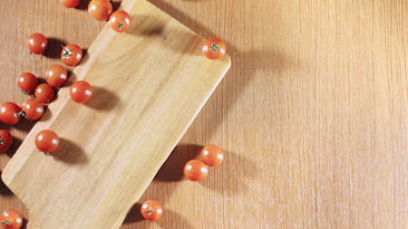 Tomatoes in cutting board with wood background