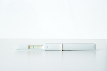 conceive: White plastic positive pregnancy test on white background