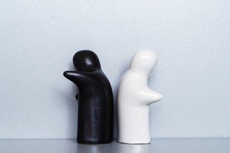 Two ceramic figures on a gray background