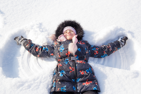 Little child girl playing in a clear white snow day