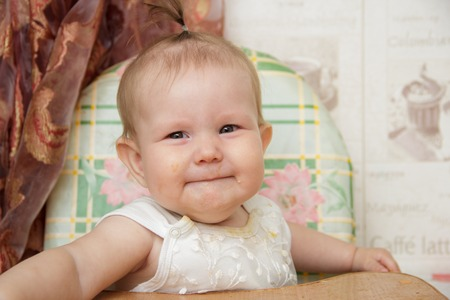 Little child girl sits in a highchair in the kitchen and eats cookies Stock Photo