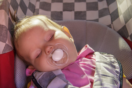 little newborn baby girl rests in the car seat in car Stock Photo