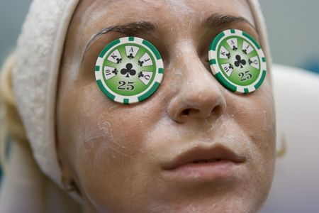 Poker chips lying on eyes like cucumbers in spa salon Stock Photo - 4318959