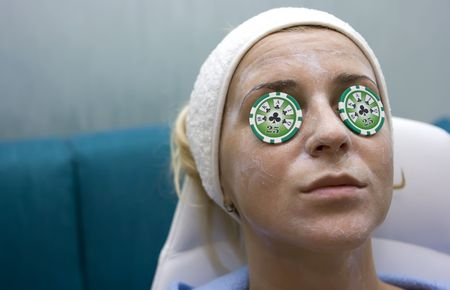 Poker chips lying on eyes like cucumbers in spa salon Stock Photo