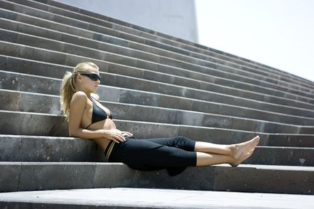 blondy: Model girl comfortably sitting on the marble stairs