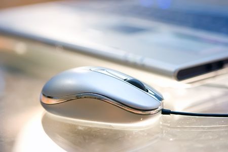 Computer mouse and notebook on dusty glass table photo