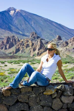 Pretty girl in shirt and jeans sitting on stone wall