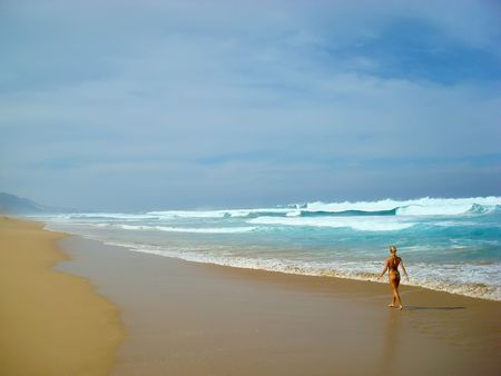 Young lady walking alone along the beach photo