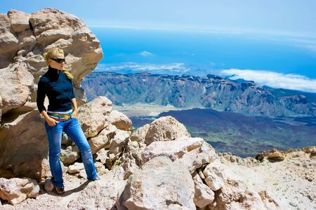Girl standing on the edge of the volcano Stock Photo