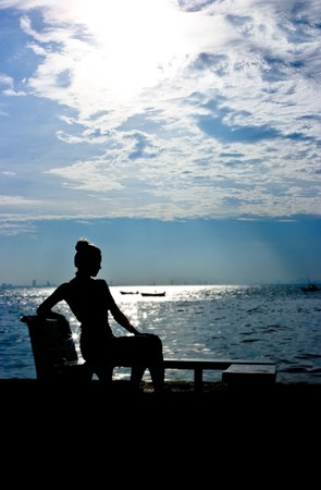 Silhouette of a young woman sitting at the ocean
