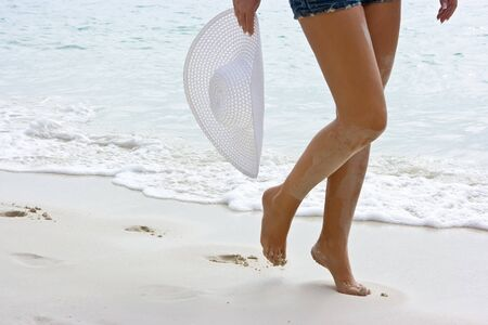 Long legged girl walking along the white sand beach Stock Photo