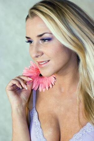 Blond girl with chrysanthemum in studio shot