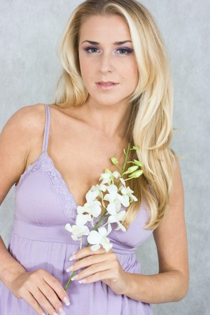 likeable: Blond girl with orchid in studio shot