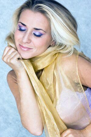 Blond beauty in silk scarf in studio shot