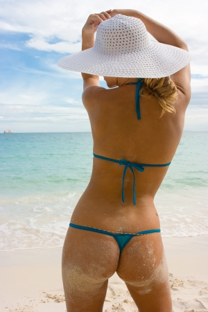 Girl in white hat on the beach