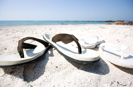 Two pair of slippers on the beach