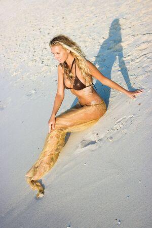 Blond girl lying on the sand beach photo