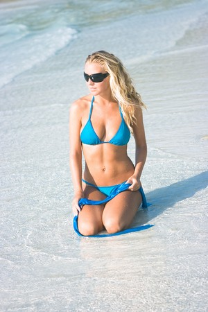Blond girl in sunglasses sitting on the beach photo