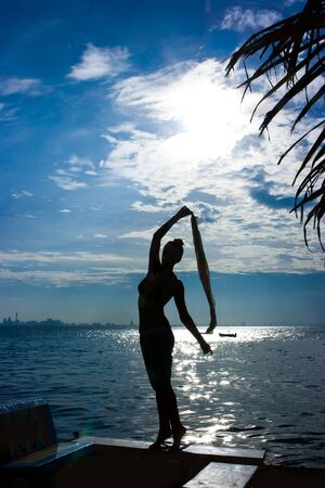 Silhouette of a girl standing at the sea