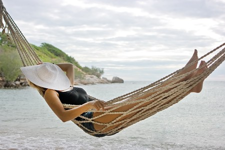 Lady with white hat lying in hammock on the sea beach