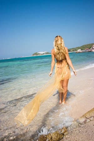Blonde girl on the beach and looks at the sea photo