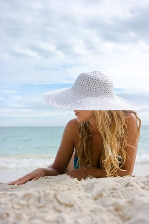 Beautiful blonde lying on white sand beach in hat
